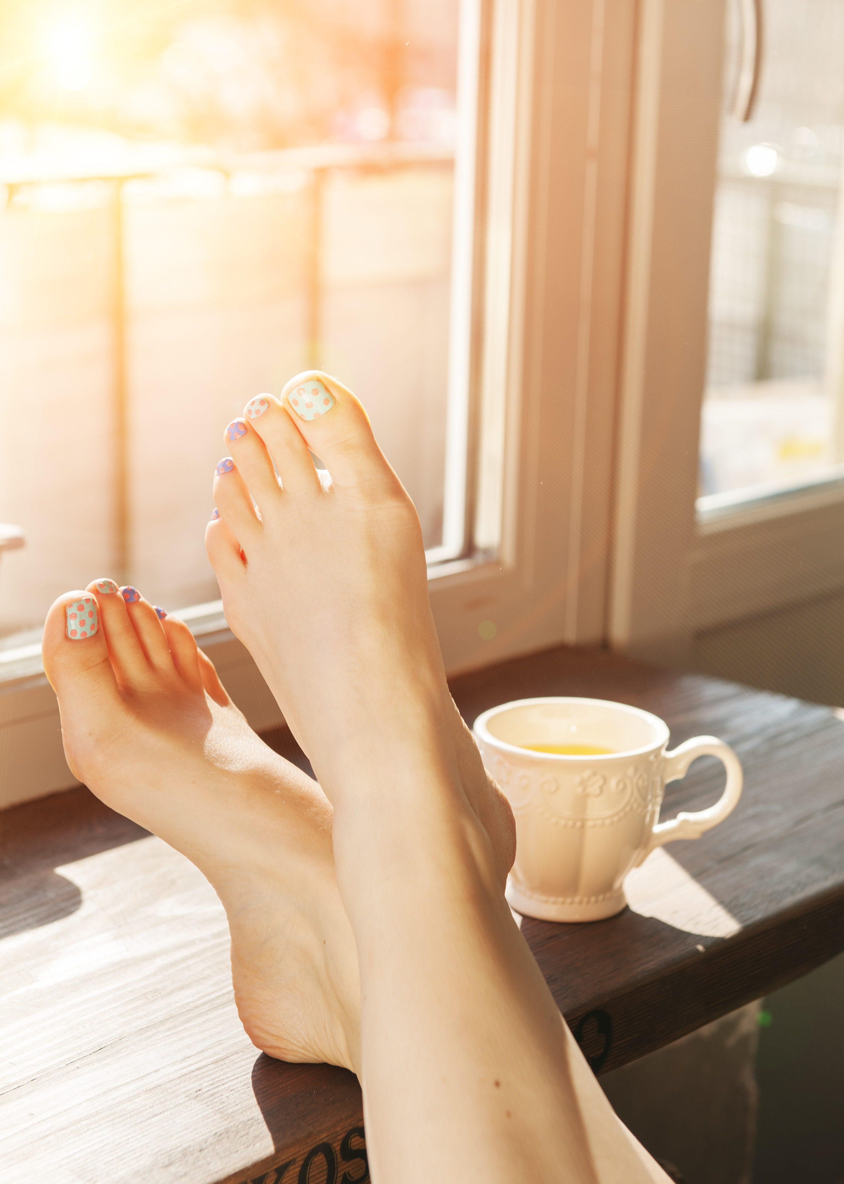 Woman feet on the window sill in sunlight. Relax concept